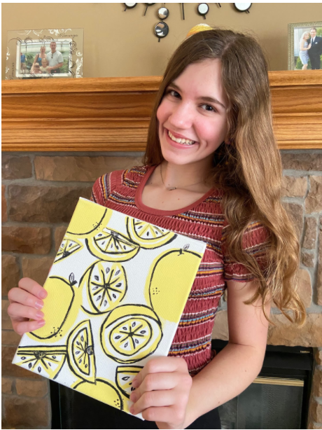 Freshman Jessica Reece shows off her lemon painting.
