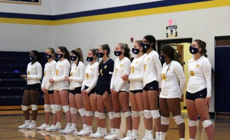 Varsity players stand for the national anthem wearing their team masks. The masks were required any time players were off the court.