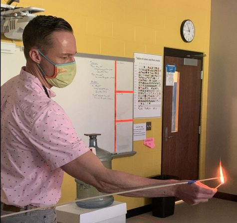 Chemistry teacher Matthew Featherstun lights wooden splint. He is creating a reaction between oxygen and ethanol.