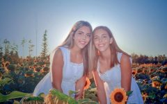 Senior identical twins Allison and Julia Laudato capture a moment in the Prayers from Maria sunflower field in Avon. Although they may look similar, they have different future paths. (Photo courtesy of Pauline Dierkens)