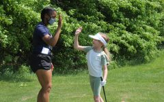 Junior Courtney Morgan gives one of the youth golfers a high five May 23 during the last session of the program. (photo by Abigail Myers)