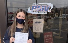 Sophomore Karly Reger holds her temporary permit in front of the BMV January 12. She plans to take her driver's test in July.