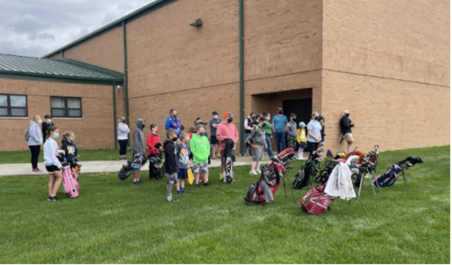 Young golfers gather with Rocket athletes and coaches outside of the annex for a practice session.